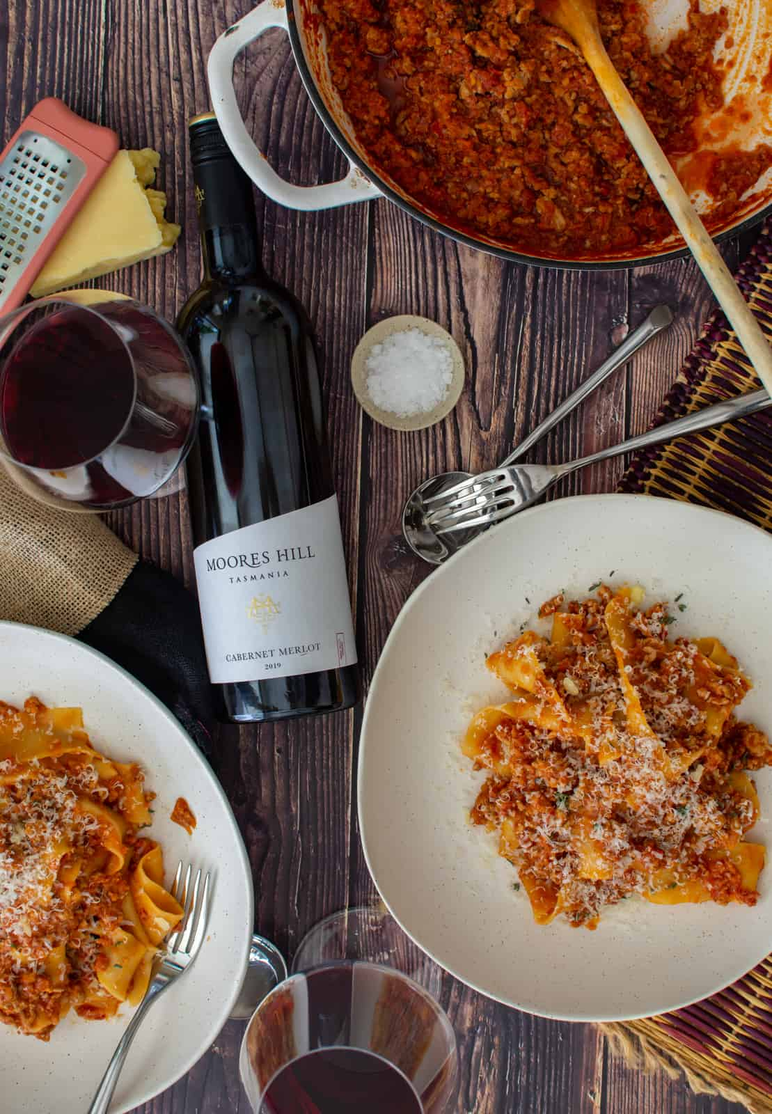 finsihed pork chorizo ragu in bowls, casserole dish and red wine on the table