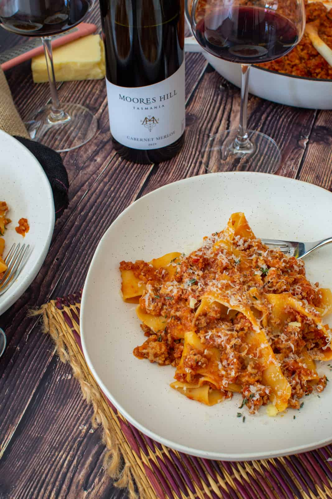 a bowl of pork chorizo ragu, moores hill red wine and casserole dish on a wooden table