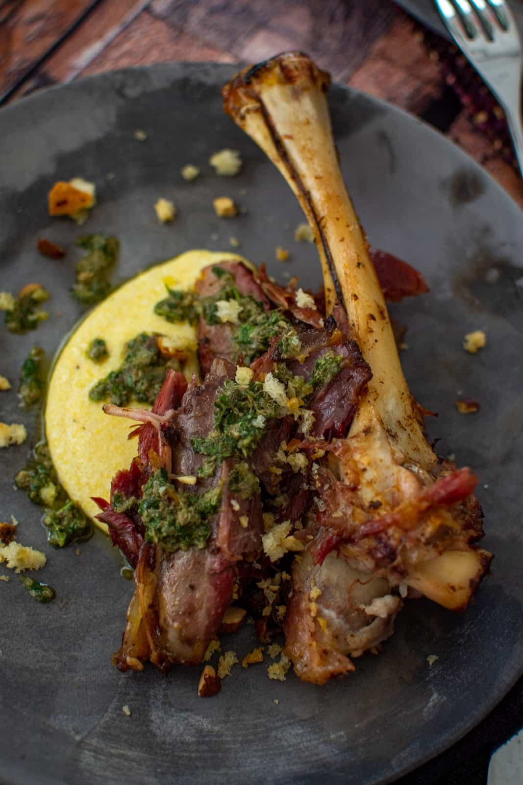 smoked lamb shank on a plate with polenta and anchovy dressing