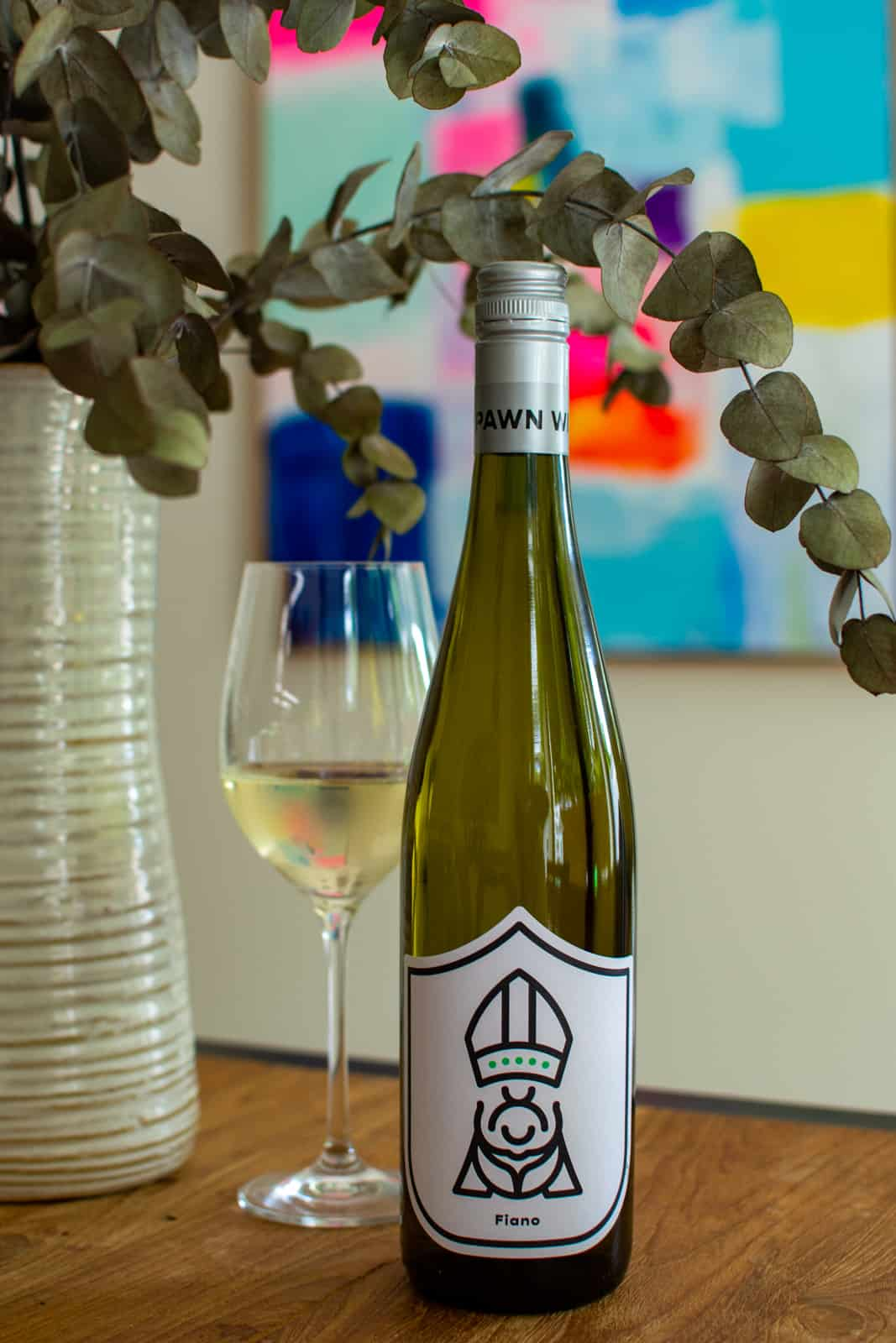 The Pawn Wine Co Fiano wine on a table with glass of wine next to it