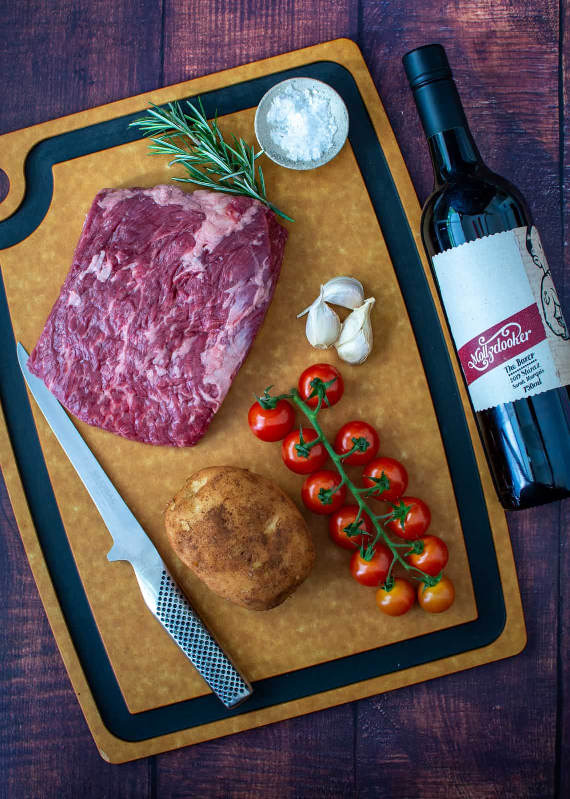 bavette steak, tomatoes & potato on chopping board. Red wine next to it