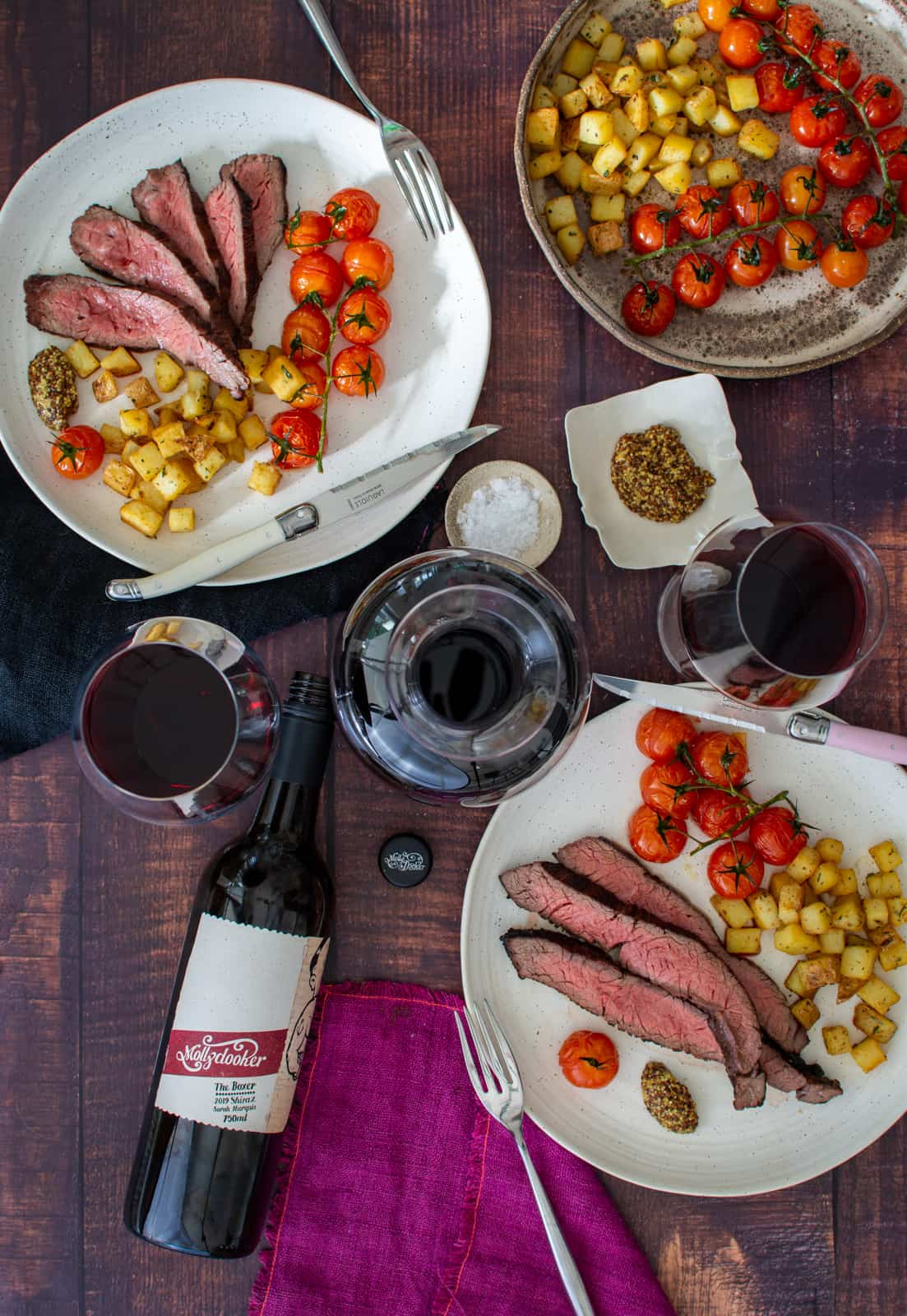 Birds eye view of bavette steak, potatoes & tomatoes on a plate with mollydooker red wine on table