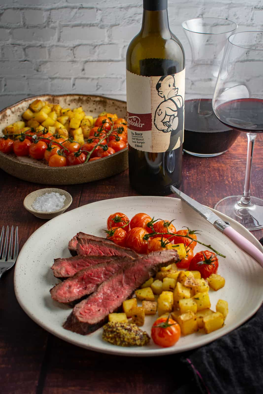 bavette steak, potatoes & tomatoes on a plate. Mollydooker red wine and wine glass in background