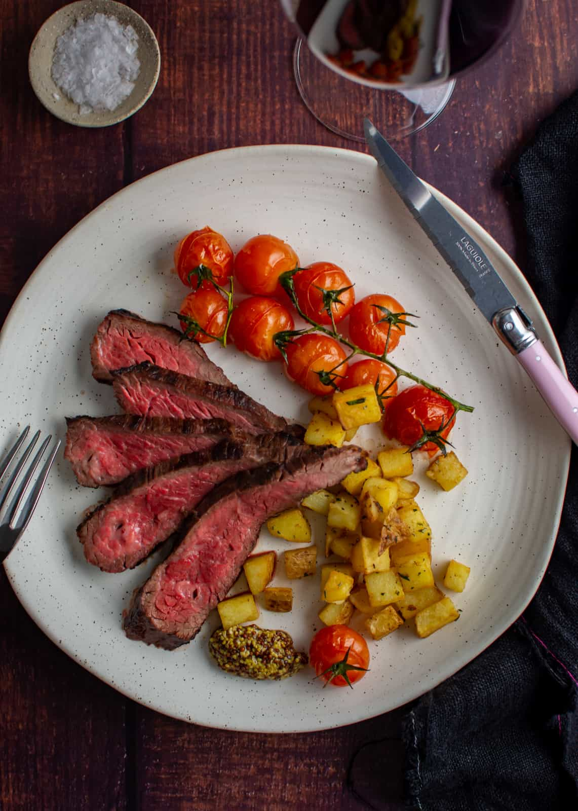 bavette steak, parmentier potatoes & tomatoes on a white plate