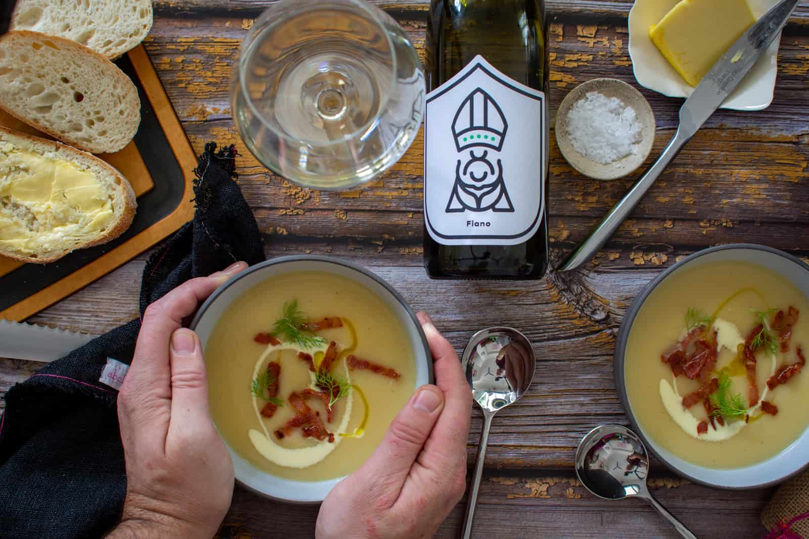 Two bowls of parsnip soup on a table with someone holding one of the bowls, bread, white wine, butter and salt also on the table
