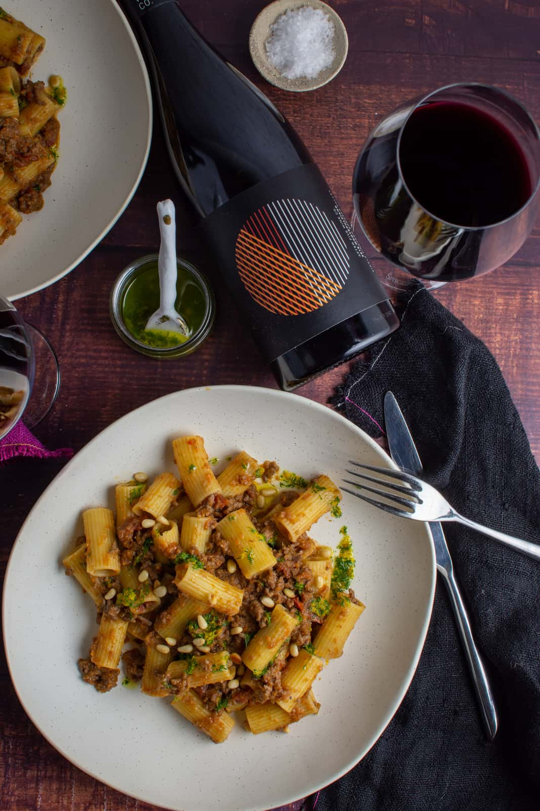 bowl of la,b ragu pasta on a table with black napkin and red wine next to it