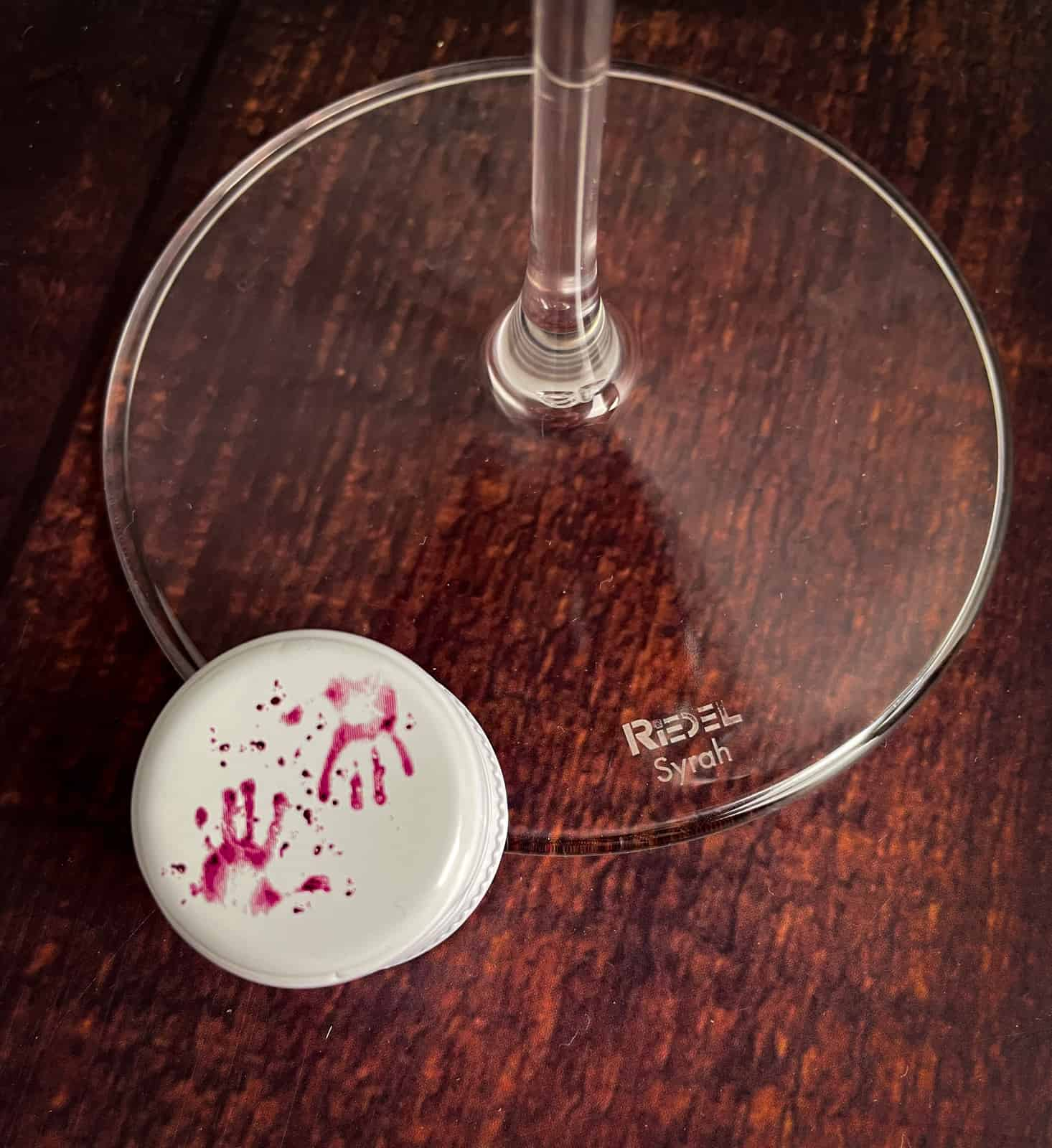 close up of purple hands bottle cap and riedel wine glass