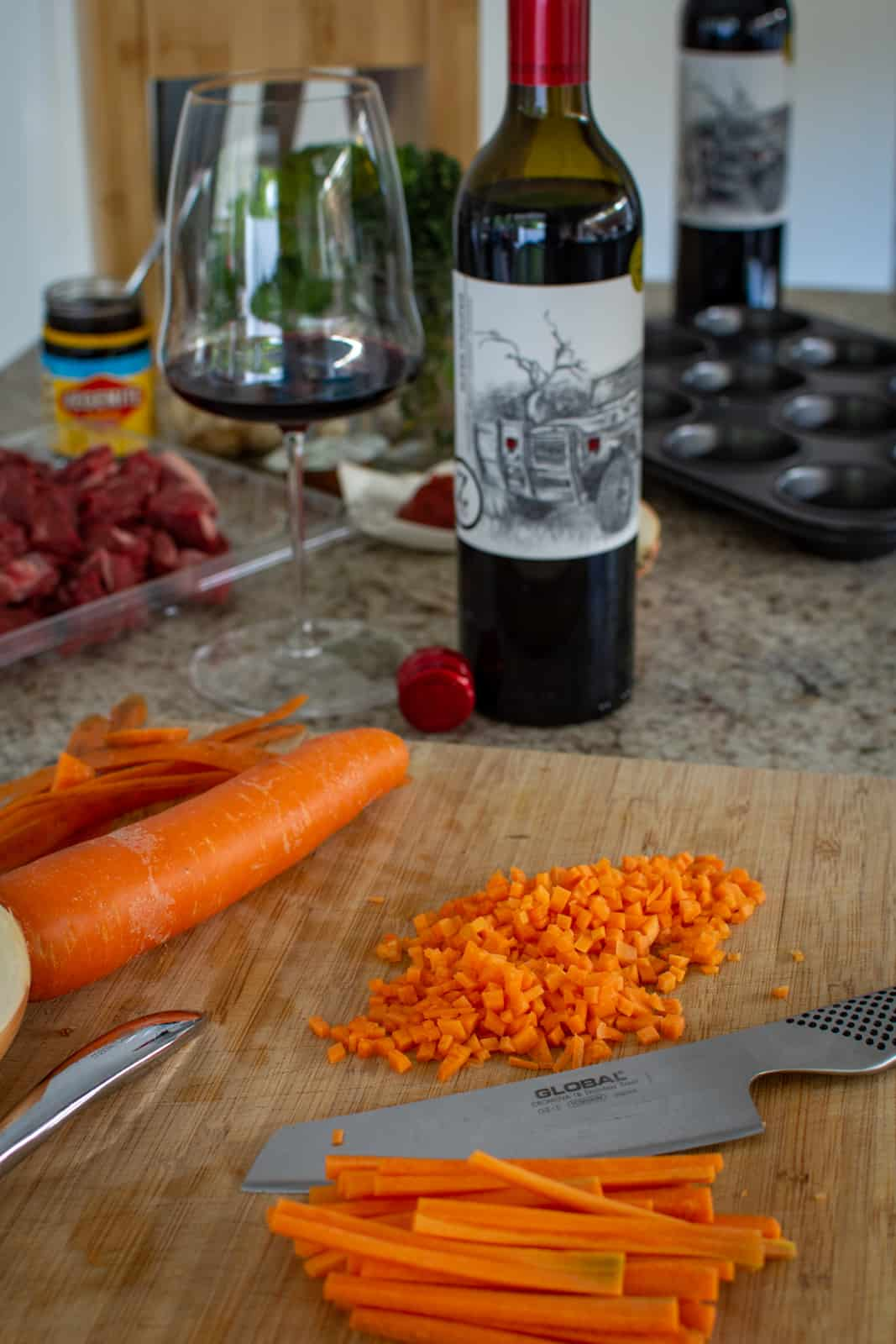 carrots being chopped on chopping board with other ingredients and wine in background