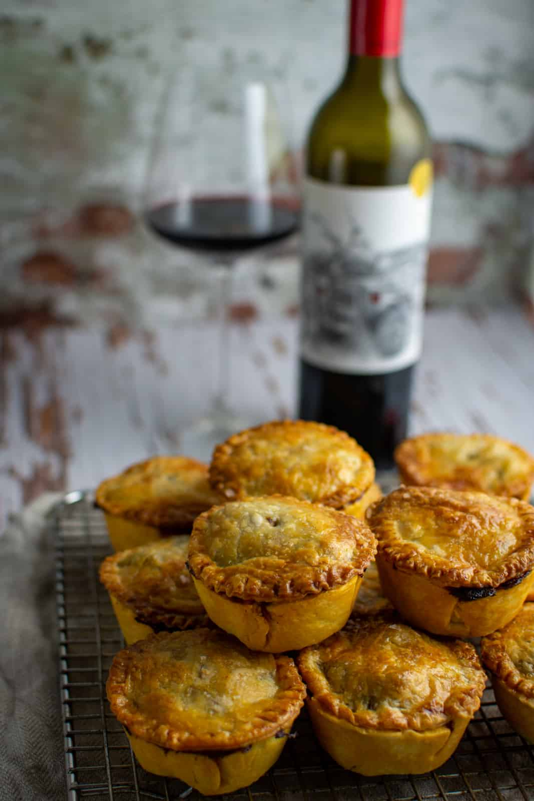 beef pies on top of each other on wire rack - wine in background