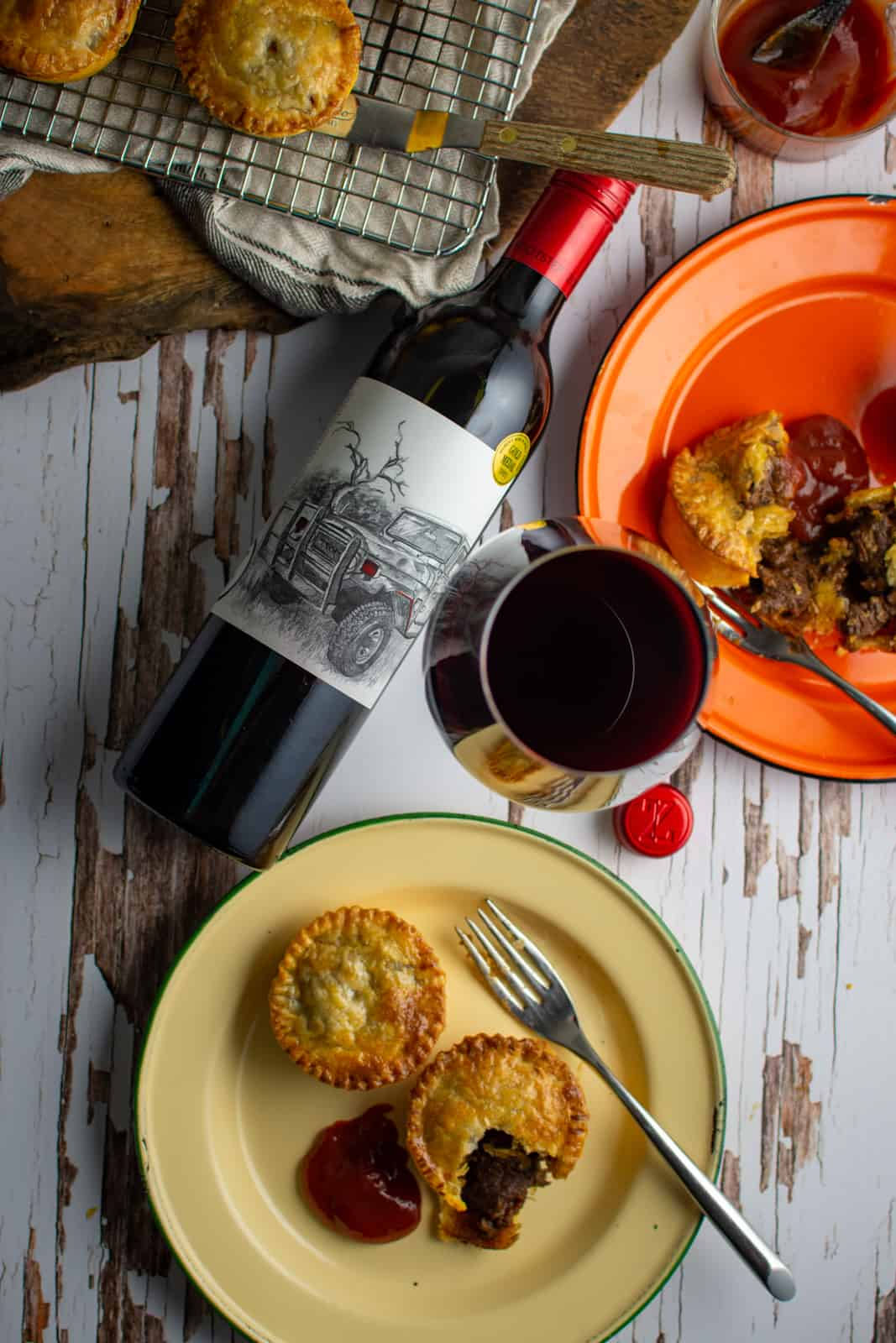 chunky beef pies on plates, red wine lying on its side and more pies on a rack