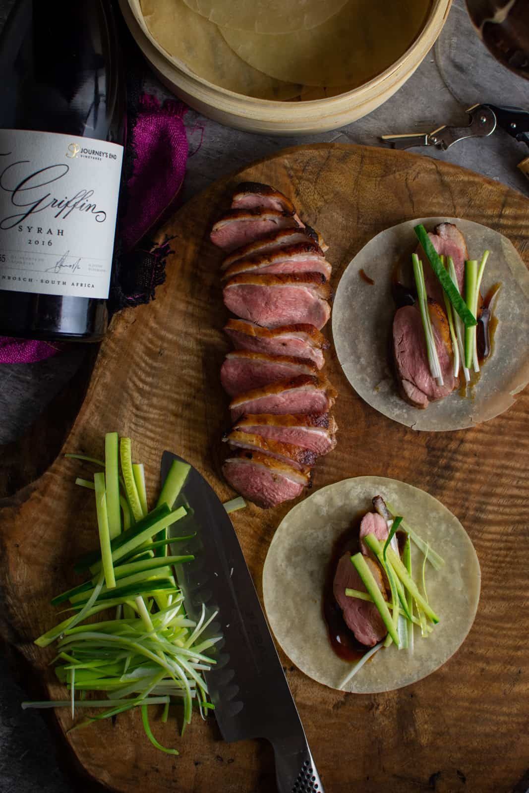 peking duck pancakes on a wooden board, duck breast and Griffin syrah next to board