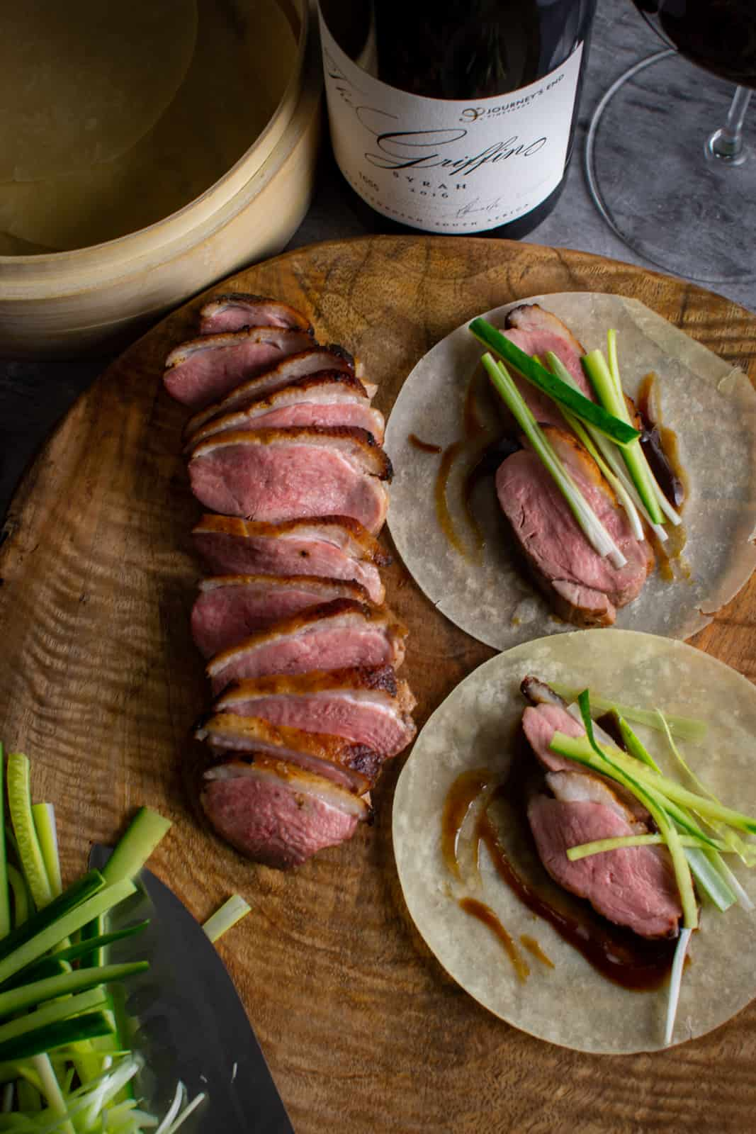 peking duck pancakes on wooden chopping board, cooked duck breast next to them with red wine too