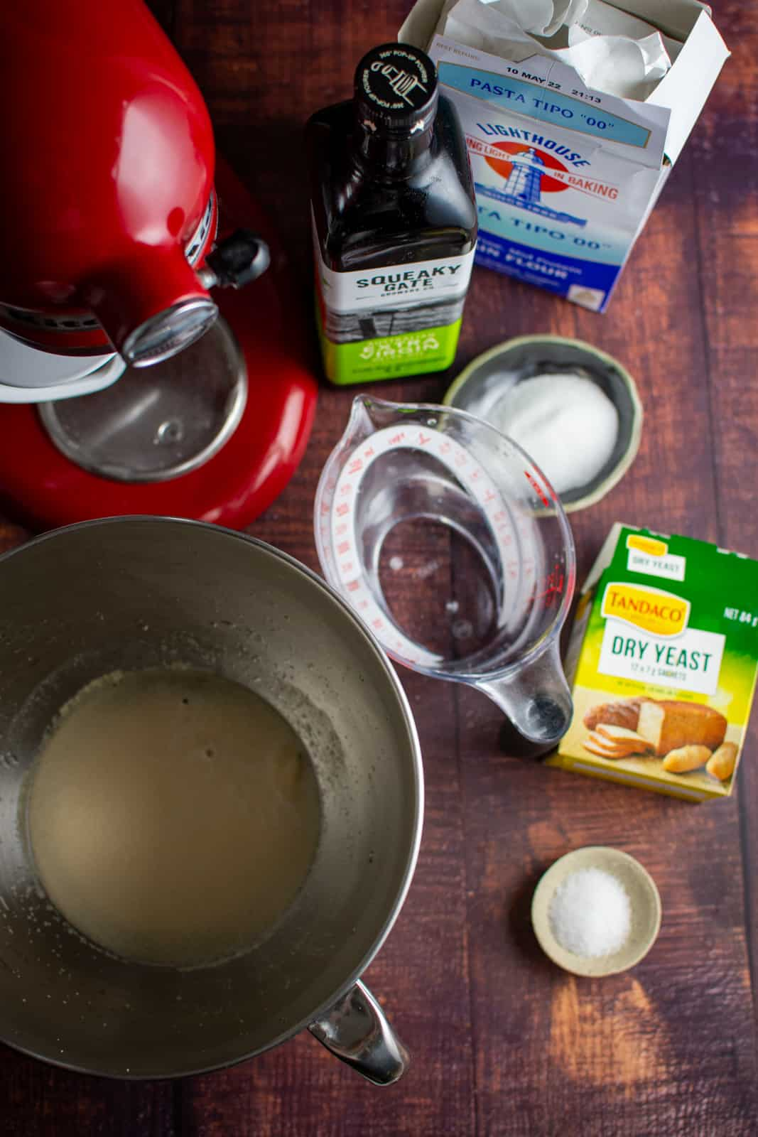 Ingredients for homemade pita, kitchen aid and warm water/yeast in a bowl