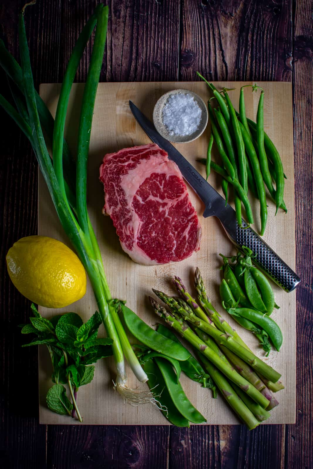 steak and mixed spring greens on a chopping board