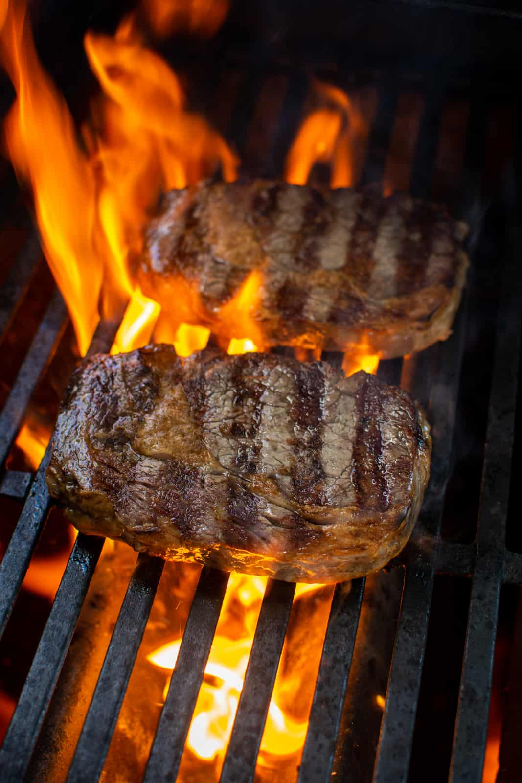 steak being grilled over gas BBQ with flames
