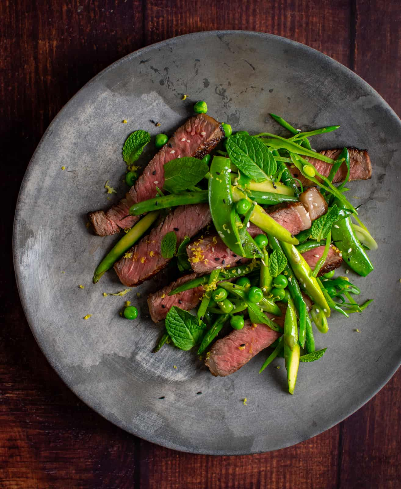 Grilled scotch steak and mixed greens salad on a plate
