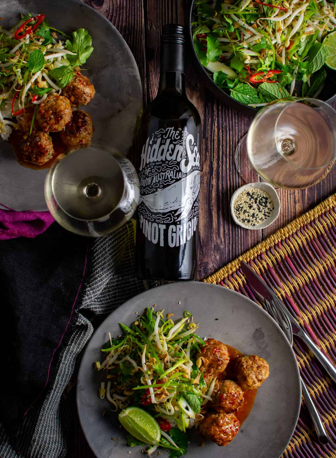 table with Asian pork meatballs, wine glasses and hidden sea pinot grigio