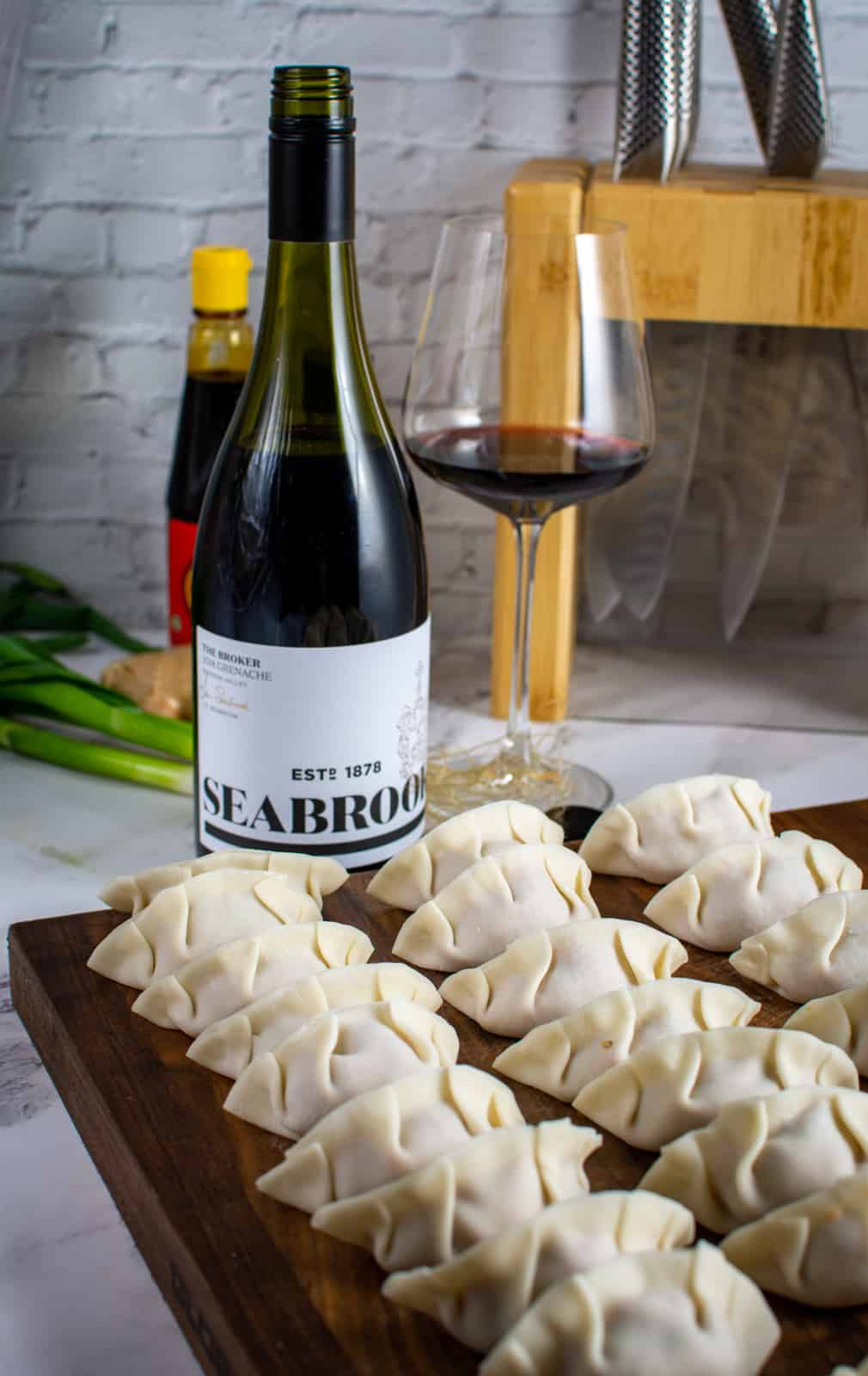 a chopping board with multiple pork cabbage dumplings and bottle of wine in background