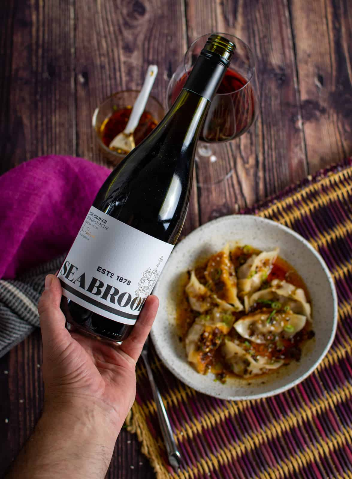 someone pouri g a glass of seabrook grenache with a bol of dumplings in the background