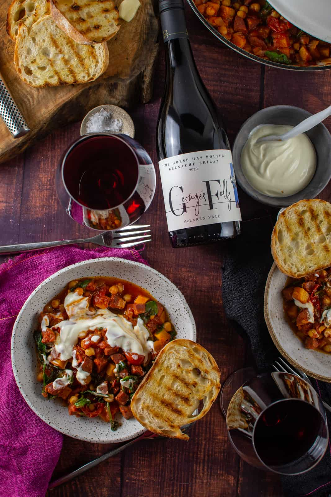 chorizo and chickpea stew on wooden table, georges folly wine and some toast