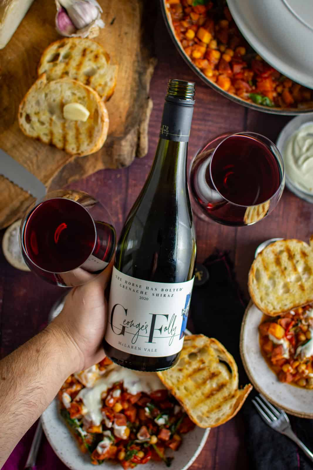 someone holding georges folly wine with food on table in background