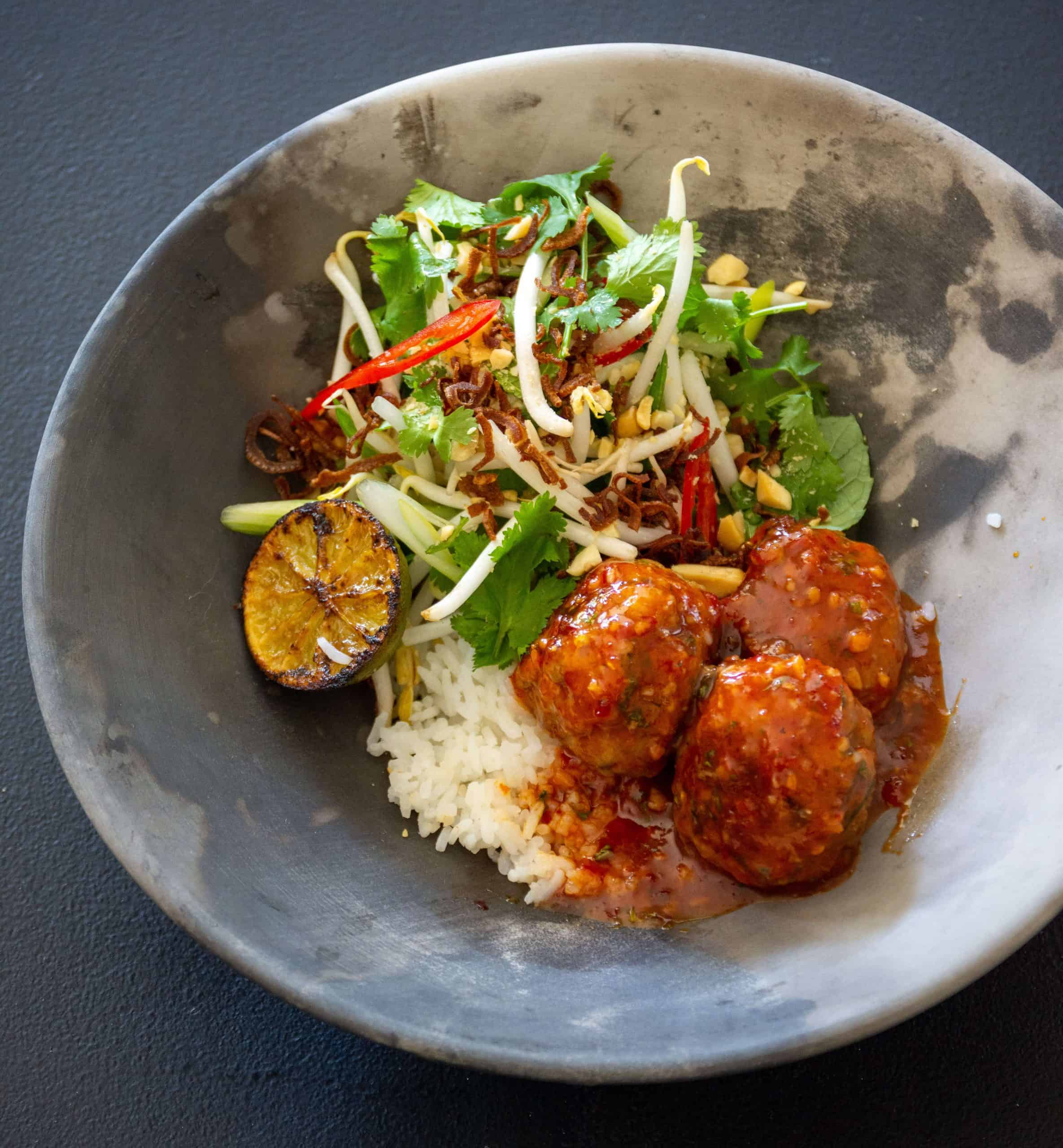 Asian pork meatballs in a bowl with rice and beansprout salad