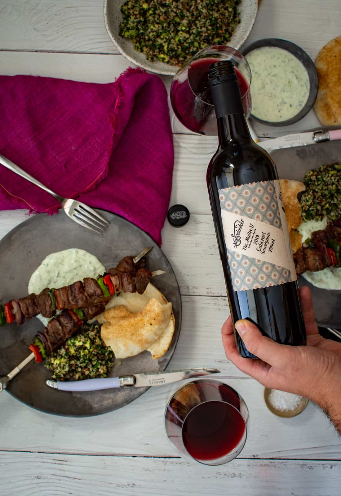 someone pouring Mollydooker red wine with grilled lamb kebabs on plates beside the wine