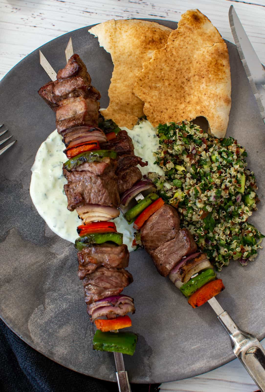 grilled lamb kebabs, tabbouleh, yoghurt dressing and pita on a plate