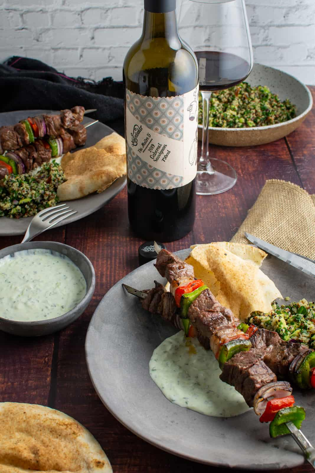 grilled lamb kebabs on a plate with yoghurt dressing, pita and red wine in backgrund