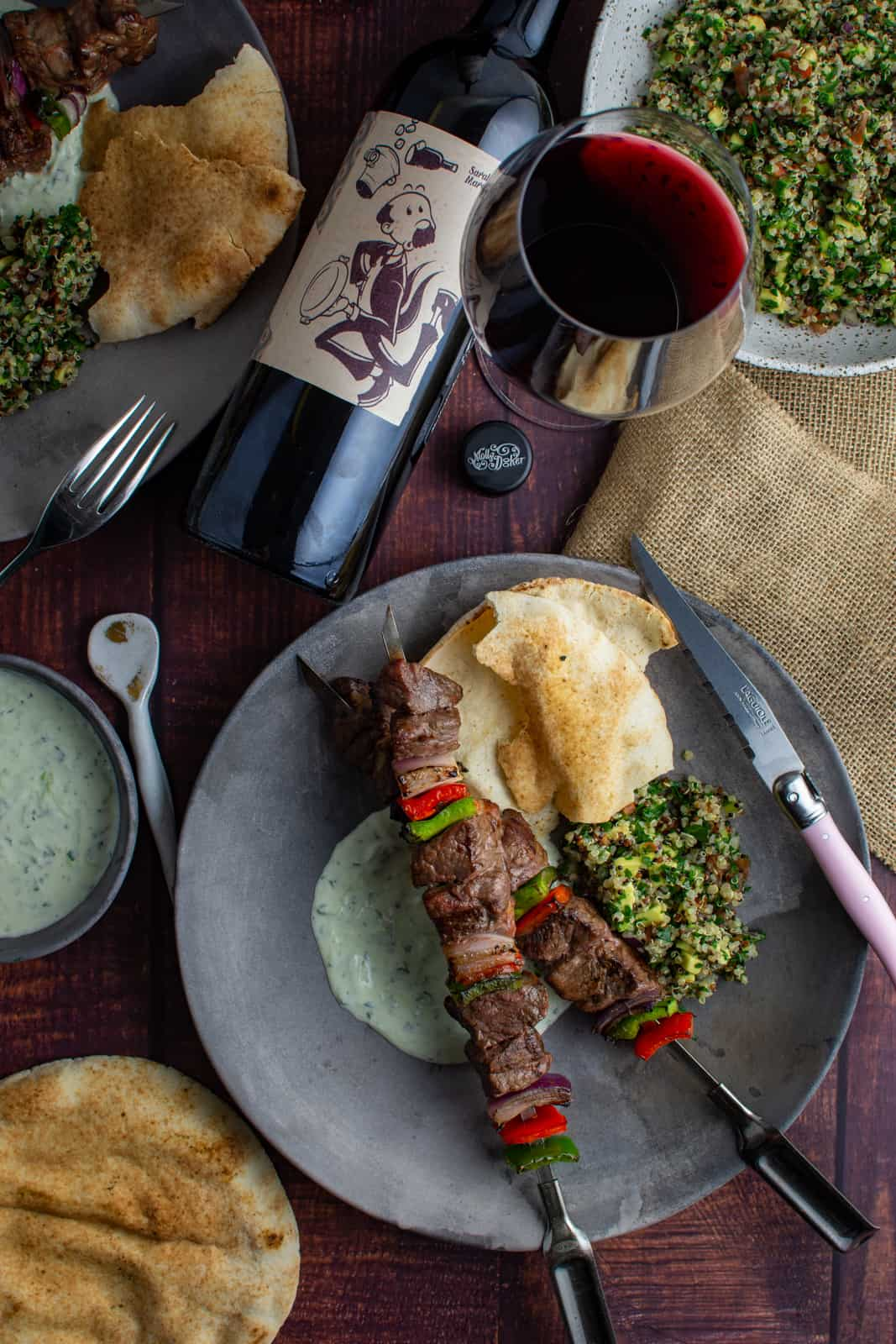 birdseye view of lamb kebabs on a plate with tabbouleh, yoghurt dressing and pita